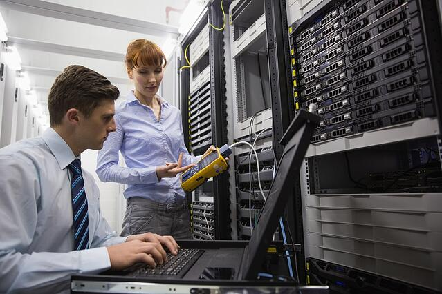 Team of technicians using digital cable analyser on servers in large data center.jpeg